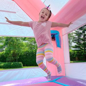 girl jumping in unicorn bounce house